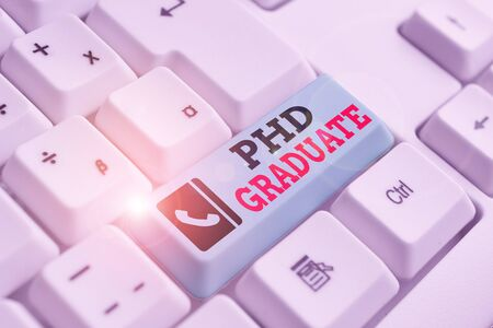 Text sign showing Phd Graduate. Business photo text highest university degree that is conferred after a course White pc keyboard with empty note paper above white background key copy space Stock fotó