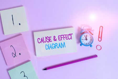 Writing note showing Cause And Effect Diagram. Business concept for Visualization tool to categorize potential causes Blank notepads marker rubber band alarm clock clip colored background Stock Photo