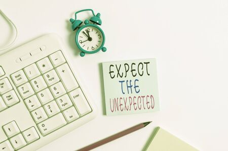 Conceptual hand writing showing Expect The Unexpected. Concept meaning Anything can Happen Consider all Possible Events Keyboard with empty note paper and pencil white background