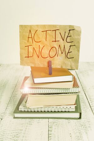 Writing note showing Active Income. Business concept for Royalties Salaries Pensions Financial Investments Tips pile stacked books notebook pin color reminder white wooden