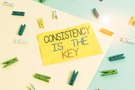 Handwriting text writing Consistency Is The Key. Conceptual photo full Dedication to a Task a habit forming process Colored clothespin paper empty reminder yellow blue floor background office Foto de archivo