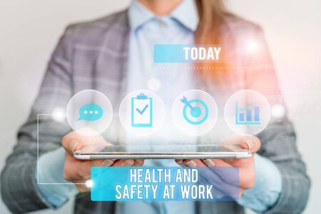 Writing note showing Health And Safety At Work. Business concept for Secure procedures prevent accidents avoid danger Female human wear formal work suit presenting smart device