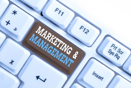 Writing note showing Marketing And Management. Business concept for process of developing strategies for product White pc keyboard with note paper above the white background Banco de Imagens - 131238027