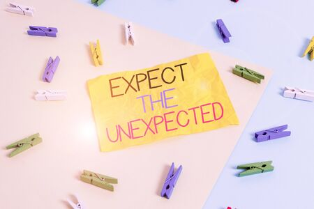 Handwriting text writing Expect The Unexpected. Conceptual photo Anything can Happen Consider all Possible Events Colored clothespin paper empty reminder yellow blue floor background office