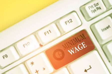 Text sign showing Minimum Wage. Business photo showcasing the lowest wage permitted by law or by a special agreement White pc keyboard with empty note paper above white background key copy space
