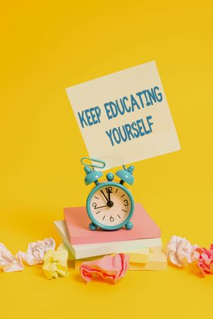 Text sign showing Keep Educating Yourself. Business photo showcasing dont stop studying Improve yourself using Courses Alarm clock sticky note paper balls stacked notepads colored background
