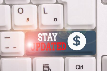 Writing note showing Stay Updated. Business concept for keep modern recent or containing the latest information White pc keyboard with note paper above the white background