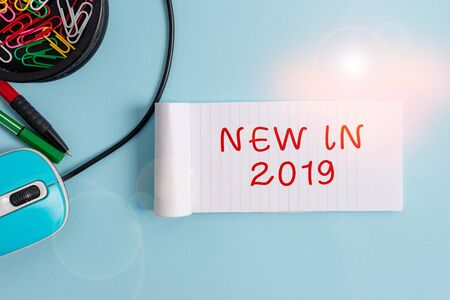 Handwriting text New In 2019. Conceptual photo what will be expecting or new creation for the year 2019 Notebook and writing equipment with computer mouse above pastel backdrop