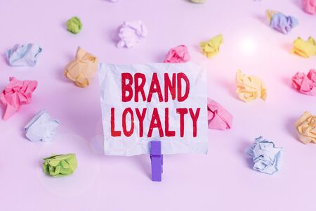 Handwriting text Brand Loyalty. Conceptual photo Repeat Purchase Ambassador Patronage Favorite Trusted Colored crumpled papers empty reminder white floor background clothespin