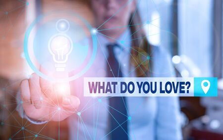 Text sign showing What Do You Love Question. Business photo showcasing Enjoyable things passion for something inspiration Female human wear formal work suit presenting presentation use smart device