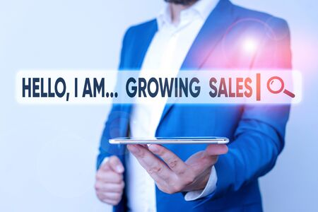 Text sign showing Hello I Am Growing Sales. Business photo showcasing Making more money Selling larger quantities Man in the blue suite and white shirt holds mobile phone in the hand Foto de archivo