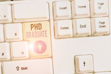 Word writing text Phd Graduate. Business photo showcasing highest university degree that is conferred after a course White pc keyboard with empty note paper above white background key copy space