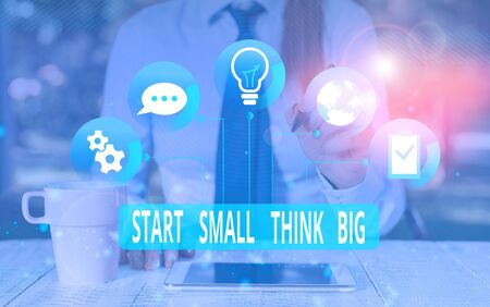Text sign showing Start Small Think Big. Business photo text Initiate with few things have something great in mind Female human wear formal work suit presenting presentation use smart device Stok Fotoğraf