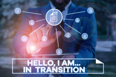 Handwriting text writing Hello I Am In Transition. Conceptual photo Changing process Progressing planning new things Male human wear formal work suit presenting presentation using smart device