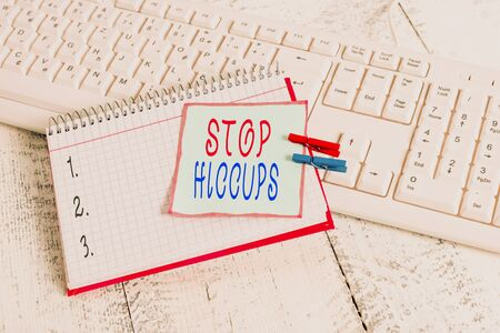 Conceptual hand writing showing Stop Hiccups. Concept meaning get rid of the involuntary spasm of the diaphragm muscles notebook reminder clothespin with pinned sheet light wooden