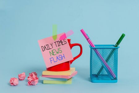 Word writing text Daily Times News Flash. Business photo showcasing fast response to actions happened in article way Cup pens holder note banners stacked pads paper balls pastel background Stock fotó