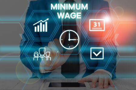 Text sign showing Minimum Wage. Business photo text the lowest wage permitted by law or by a special agreement Male human wear formal work suit presenting presentation using smart device Фото со стока