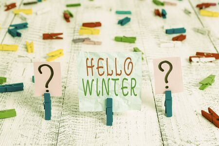 Conceptual hand writing showing Hello Winter. Concept meaning coldest season of the year in polar and temperate zones Crumbling sheet with paper clips placed on the wooden table