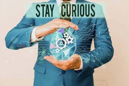Conceptual hand writing showing Stay Curious. Concept meaning attention through being inexplicable or highly unusual Male human wear formal suit presenting using smart device 免版税图像