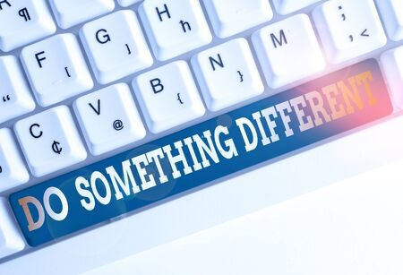 Text sign showing Do Something Different. Business photo text be unique Think outside of the box Have some fun White pc keyboard with empty note paper above white background key copy space Фото со стока