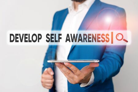 Text sign showing Develop Self Awareness. Business photo showcasing increase conscious knowledge of own character Man in the blue suite and white shirt holds mobile phone in the hand