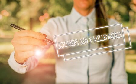 Word writing text Boomers Gen X Millennials. Business photo showcasing generally considered to be about thirty years Woman in a blue business shirts pointing with her finger into empty space Stok Fotoğraf