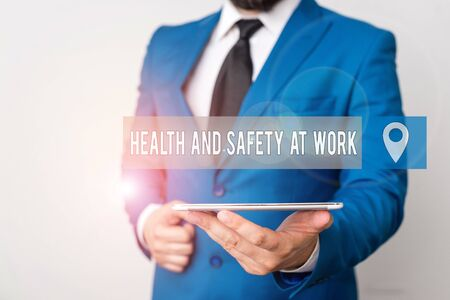Writing note showing Health And Safety At Work. Business concept for Secure procedures prevent accidents avoid danger Businessman in blue suite with a tie holds lap top in hands