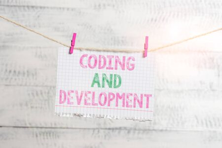 Writing note showing Coding And Development. Business concept for Programming Building simple assembly Programs Clothesline clothespin rectangle shaped paper reminder white wood desk
