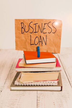 Writing note showing Business Loan. Business concept for Credit Mortgage Financial Assistance Cash Advances Debt pile stacked books notebook pin color reminder white wooden Banco de Imagens - 131353408
