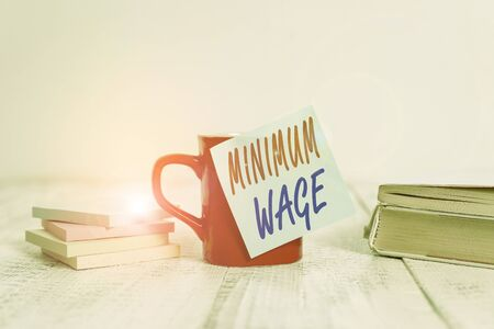 Text sign showing Minimum Wage. Business photo text the lowest wage permitted by law or by a special agreement Coffee cup blank sticky note stacked note pads books retro old wooden table