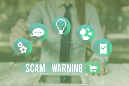 Writing note showing Scam Warning. Business concept for caution of unsolicited email claims the prospect of a bargain Female human wear formal work suit presenting smart device Stok Fotoğraf