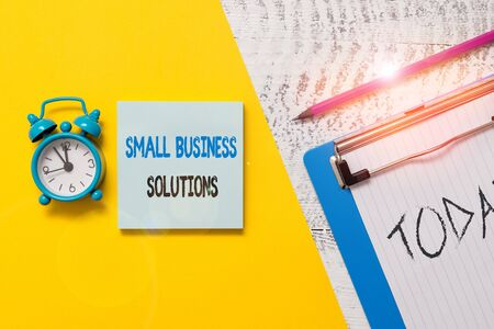 Writing note showing Small Business Solutions. Business concept for a Company to solve Specific Trade problems Notepad clipboard colored paper sheet alarm clock wooden background