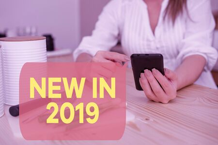 Writing note showing New In 2019. Business concept for what will be expecting or new creation for the year 2019 woman using smartphone and technological devices inside the home