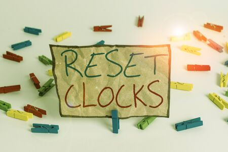 Word writing text Reset Clocks. Business photo showcasing To revisit return to or recreate a time or era from the past Colored clothespin papers empty reminder white floor background office