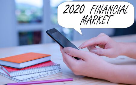 Conceptual hand writing showing 2020 Financial Market. Concept meaning place where trading of equities, bonds, currencies woman using smartphone and technological devices inside the home