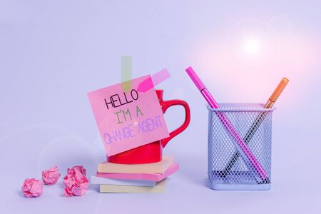 Word writing text Hello I M A Change Agent. Business photo showcasing Promoting and enabling difference evolution new Cup pens holder note banners stacked pads paper balls pastel background 写真素材