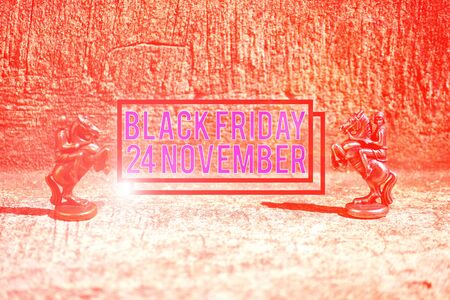 Text sign showing Black Friday 24 November. Business photo showcasing Special sales Thanksgiving discounts Clearance Two Bronze Chess Pieces Knights Facing Each Other in Focus and Defocused