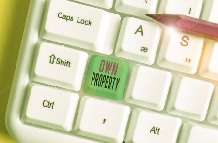 Text sign showing Own Property. Business photo showcasing Things that you own and can take it with you Movable Tangible White pc keyboard with empty note paper above white background key copy space Stok Fotoğraf