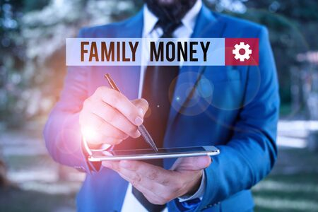 Text sign showing Family Money. Business photo showcasing the inherited wealth of established upperclass families Businessman in blue suite stands with mobile phone in hands
