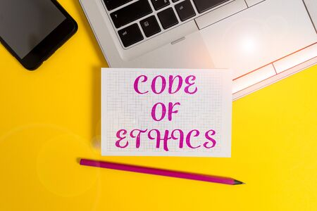 Text sign showing Code Of Ethics. Business photo text basic guide for professional conduct and imposes duties Metallic laptop pencil squared paper sheet smartphone colored background