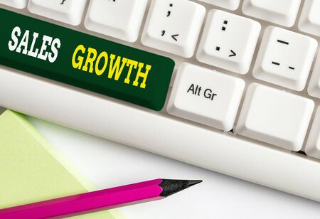 Conceptual hand writing showing Sales Growth. Concept meaning ability to increase revenue over a fixed period of time White pc keyboard with note paper above the white background Фото со стока
