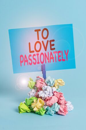 Text sign showing To Love Passionately. Business photo text Strong feeling for someone or something else Affection Reminder pile colored crumpled paper clothespin reminder blue background