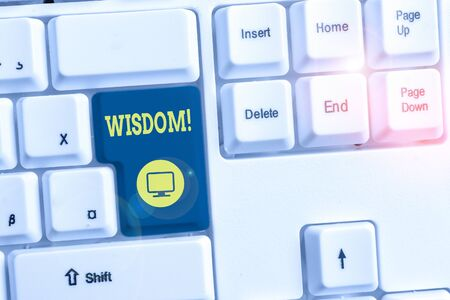 Conceptual hand writing showing Wisdom. Concept meaning the ability to use your knowledge and experience to make decisions White pc keyboard with note paper above the white background Archivio Fotografico