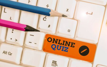 Conceptual hand writing showing Online Quiz. Concept meaning game or a mind sport that are published on the Internet White pc keyboard with note paper above the white background Banco de Imagens