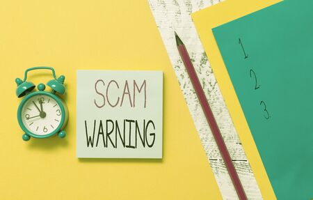 Conceptual hand writing showing Scam Warning. Concept meaning caution of unsolicited email claims the prospect of a bargain Notepads marker colored paper sheets alarm clock wooden background Stok Fotoğraf