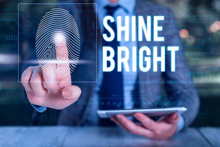 Text sign showing Shine Bright. Business photo text make an effort to live normally when in a difficult situation Woman wear formal work suit presenting presentation using smart device 写真素材