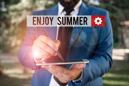 Text sign showing Enjoy Summer. Business photo showcasing taking a break from school and spending holidays in the beach Businessman in blue suite stands with mobile phone in hands