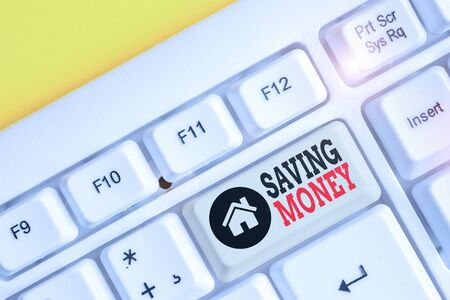 Text sign showing Saving Money. Business photo text putting money in an account in a bank o financial organization White pc keyboard with empty note paper above white background key copy space
