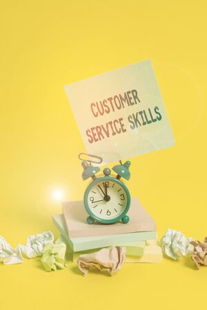 Text sign showing Customer Service Skills. Business photo showcasing Aptitude to master to improve dealings with client Alarm clock sticky note paper balls stacked notepads colored background Imagens
