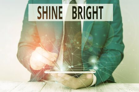 Text sign showing Shine Bright. Business photo showcasing make an effort to live normally when in a difficult situation Male human wear formal work suit presenting presentation using smart device 写真素材